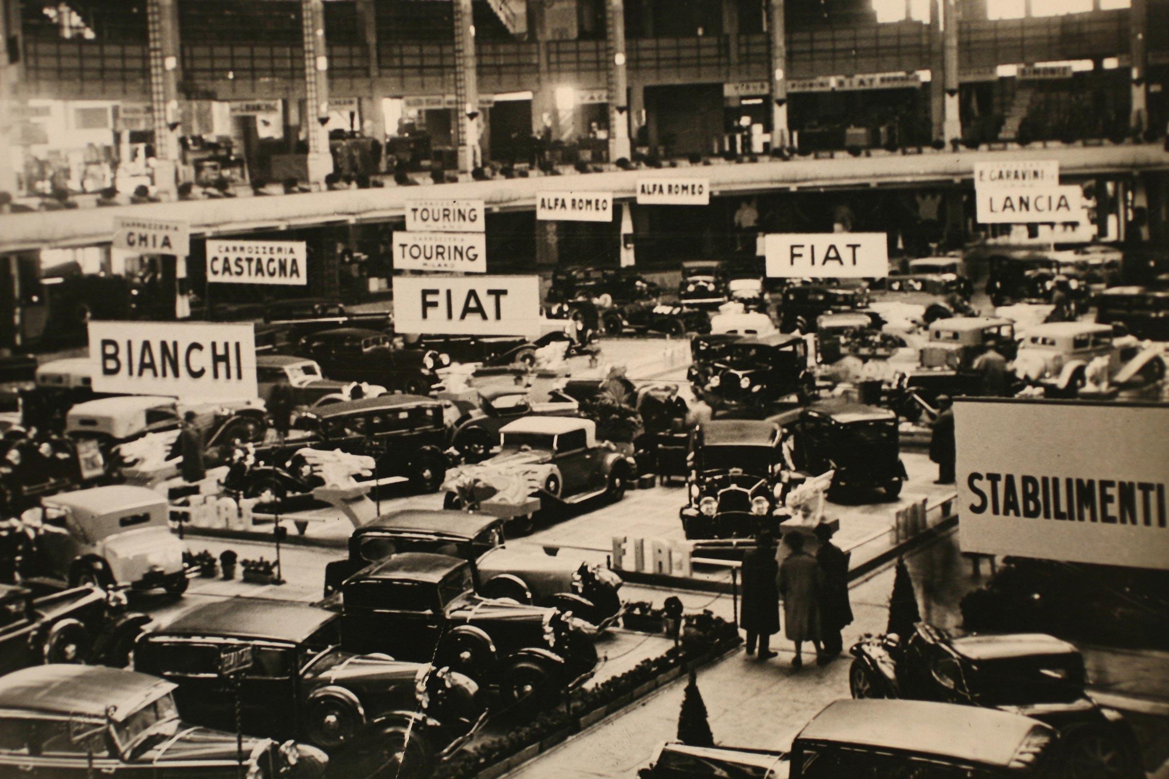 """Nel 1932 nasce la Fiat """"Balilla"""" ed è subito la star della Fiera: la vediamo sulla pedana al centro dello stand della Casa torinese. Intorno, i modelli Fiat più lussuosi, come la """"522"""" e la """"524""""."""