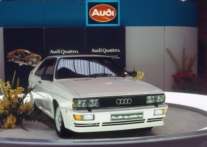 "1980: five-cylinder gasoline engine with turbocharger and intercooler: In 1980 at the Geneva Motor Show, Audi unveils the Audi quattro (B2), known as the ""Ur-quattro"" from the mid-1990s. It uses the powerplant from the Audi 200 5T (C2), but features an intercooler. As a result, the turbocharged engine achieves a higher output of 147 kW (200 hp) at 5,500 revolutions per minute and 285 newton meters (210.21 lb-ft) of torque at 3,500 rpm. The body of the Audi quattro is based on the Audi Coupe (B2), which in turn is based on the Audi 80. Flared fenders, bulkier bumpers and sills as well as a larger rear spoiler distinguish the Audi quattro from the Coupe."